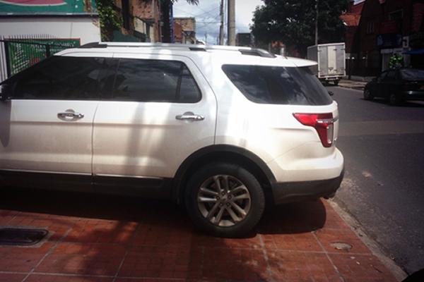 Un vehículo obstruye completamente un andén, obligando al peatón a usar la calzada.