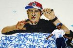 Boy plays next to graffiti depicting Venezuelan President Hugo Chavez as a rap singer in Petare in the suburbs of Caracas