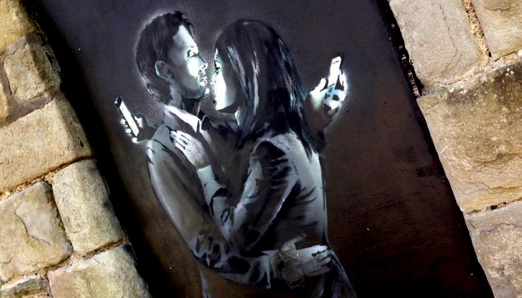 """""""Mobile lovers"""" (Amantes móviles-Amantes del celular), obra de Banksy en un club de Bristol, reproducida en el artículo """"True Slaves to Our Devices"""" (Verdaderos Esclavos de Nuestros Artefactos), publicado en adbusters.org"""