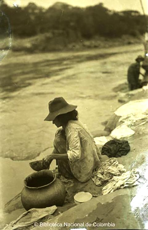 [Lavandera]. Mujer acurrucada, con sombrero, lavando ropa con totuma a la orilla de un río1950