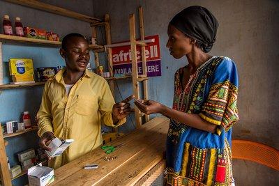 El farmacéutico Larson Manirakiza, de 29 años, aconseja a un cliente sobre un medicamento en su tienda del pueblo de Kashojwa, en Uganda.