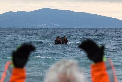 Un voluntario hace señas a una barca llena de refugiados frente a la isla griega de Lesbos.