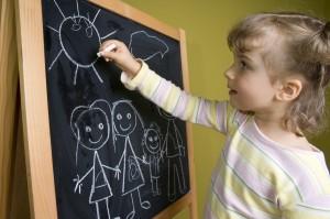 Little girl  drawing family on blackboard; education