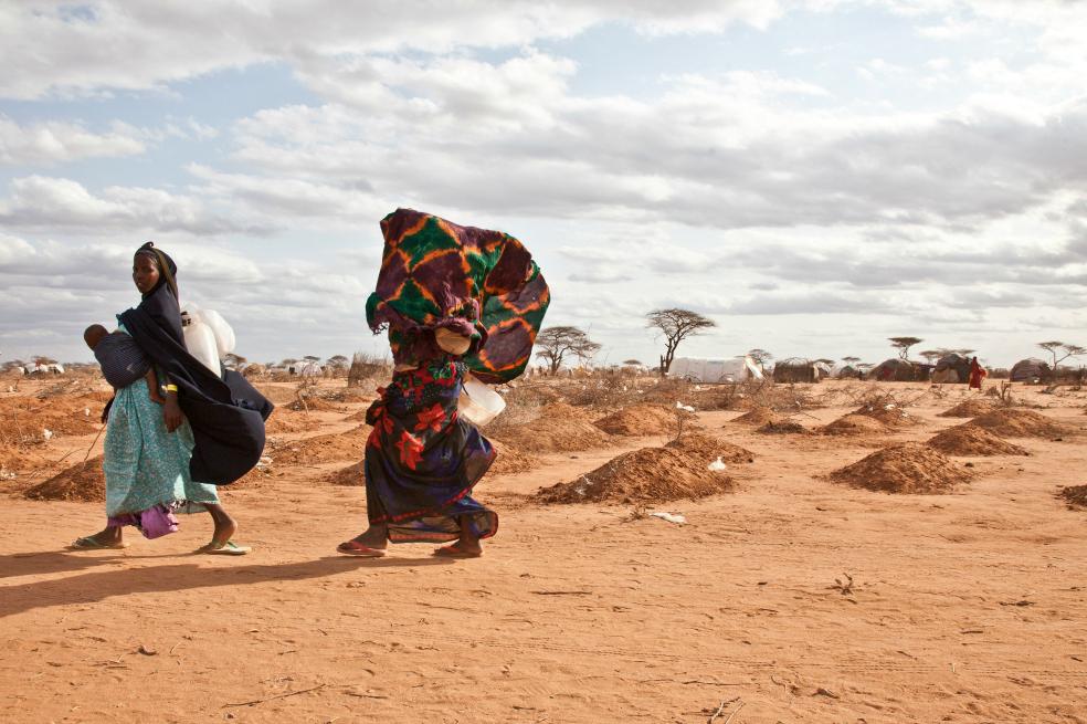 Two Somali refugee women walk past  recently dug graves in Dadaab refugee camp.