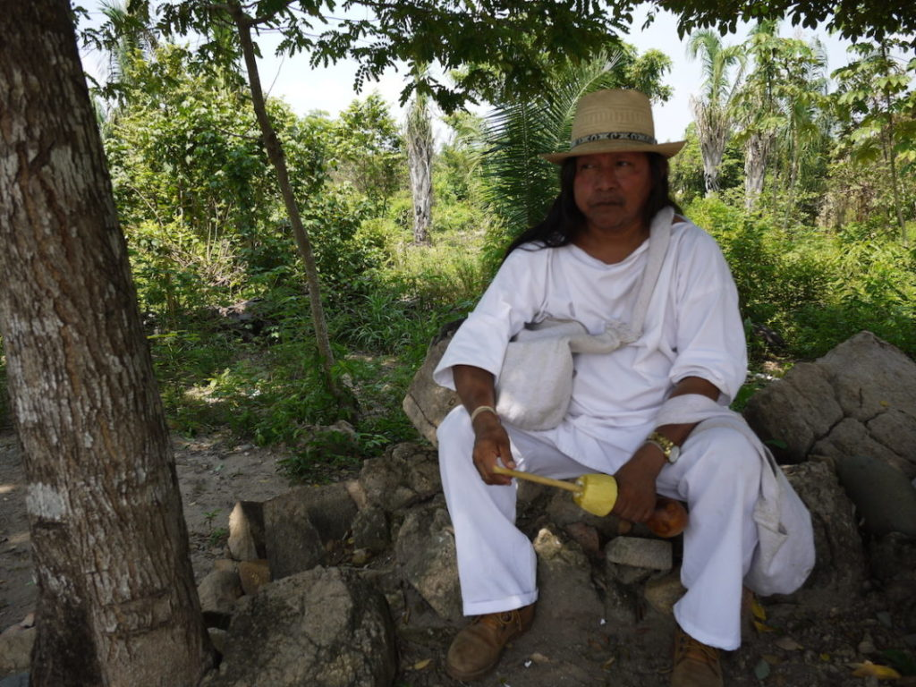 Antonio Pinto se detiene para purificarse a sí mismo en un punto en que los Wiwa consideran sagrado antes de subir las montañas. En su mano sostiene un poporo. Foto de Laura Dixon.