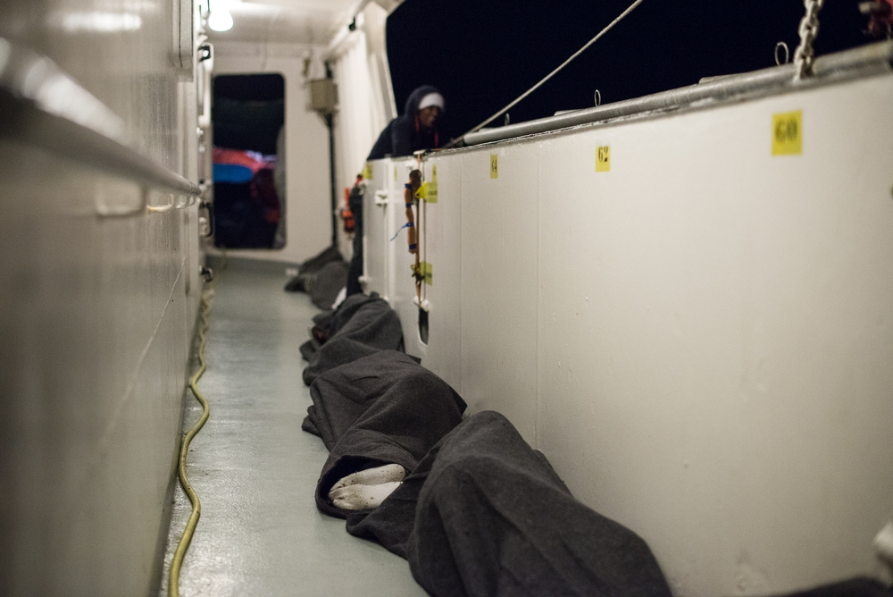 Refugees sleep on the deck of the MV Aquarius search and rescue vessel 04 October after being rescues along with 720 other the previous day. On 03 October MSF crews aboard three rescue ships, Dignity 1, Bourbon Argos and Aquarius, in the Mediterranean were involved in saving almost 2,000 from small boats off the coast of Libya.