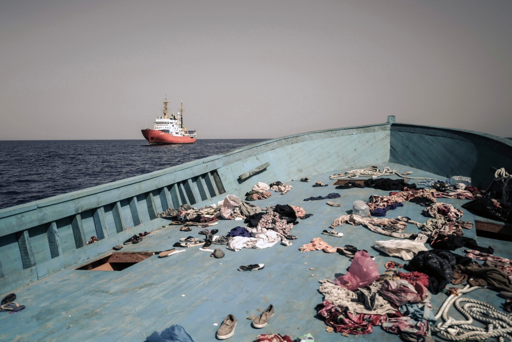 Personal effects and belongs are discarded on the deck of a small wooden boat 03 October after the passengers were rescued by the MSF MV Aquarius search and rescue vessel, seen in the background. The Médecins Sans Frontières (MSF) search and rescue teams on board the Bourbon Argos, the Dignity I and the Aquarius (run in partnership with SOS Mediteranee)rescued nearly 2000 men, women and children from 11 separate boats in less than 7 hours on 03 October. Many of the rescues were conducted in dramatic circumstances, with some patients requiring evacuation to the Italian mainland. Tragically, one young pregnant woman died after being rescued by the Dignity I and before she was able to be transferred to land.