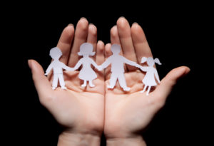 Paper chain family protected in cupped hands on black background