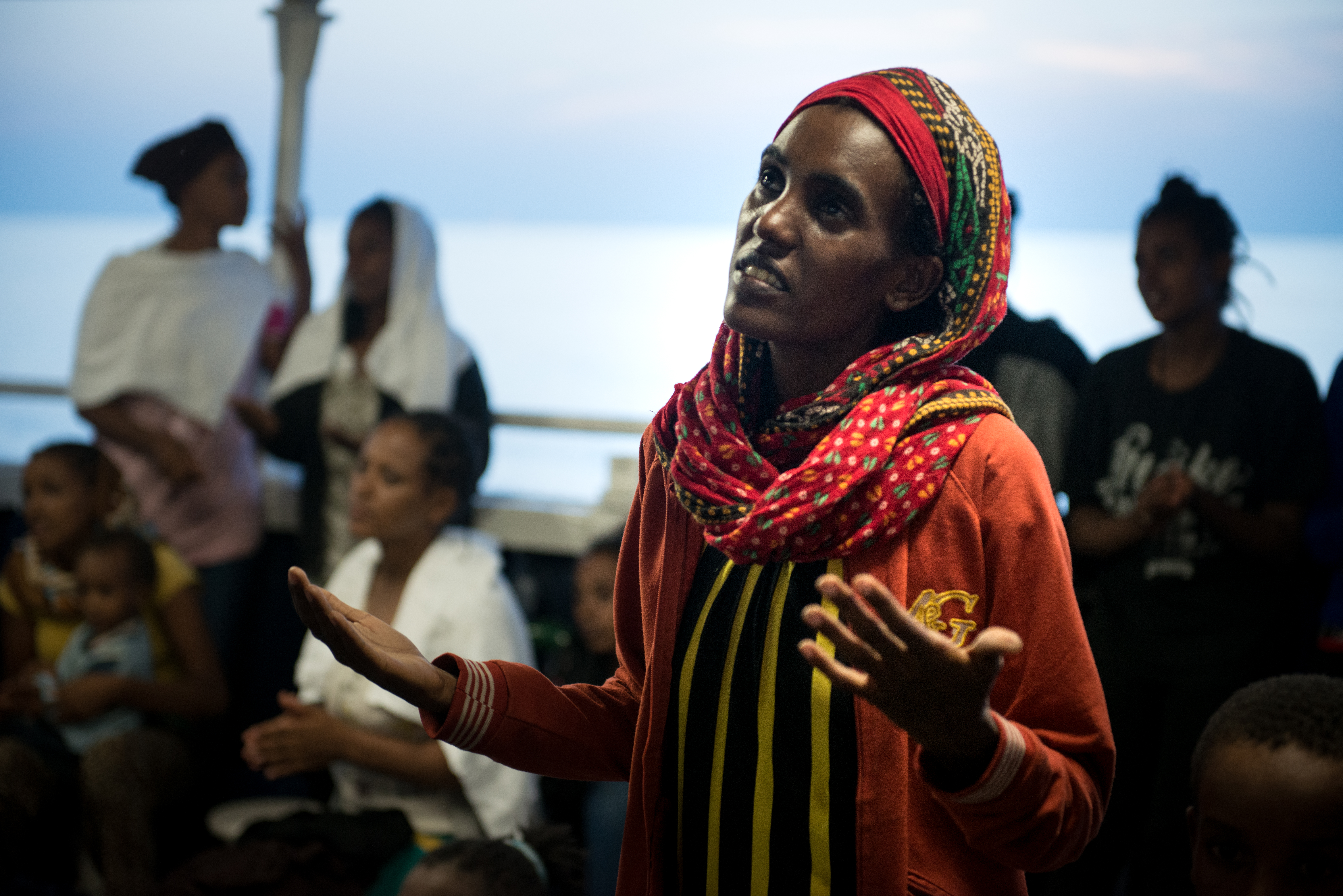 An Eritrean woman singing a prayer with other women and children after being rescued 02 September 2015 by the MSF MY Phoenix search and rescue vessel at sea.