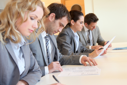 Young business people signing application form