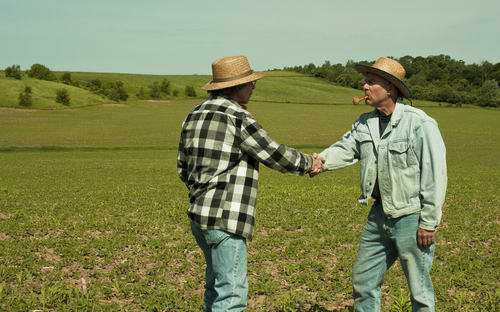 two farmers shaking hands in a field