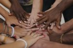Many hands together: group of people joining hands