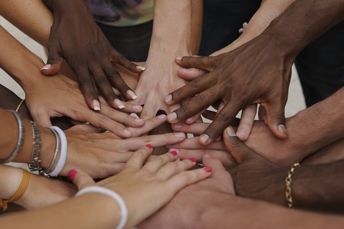 Many hands together: group of diverse people joining hands