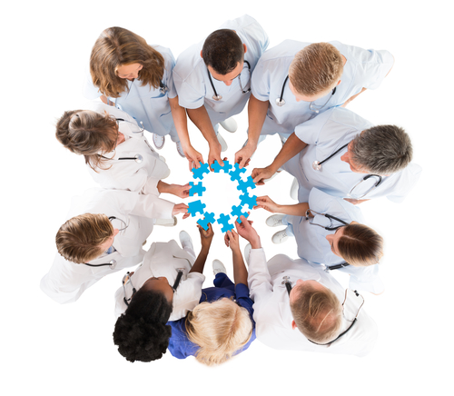 Directly above shot of medical team joining blue jigsaw pieces against white background