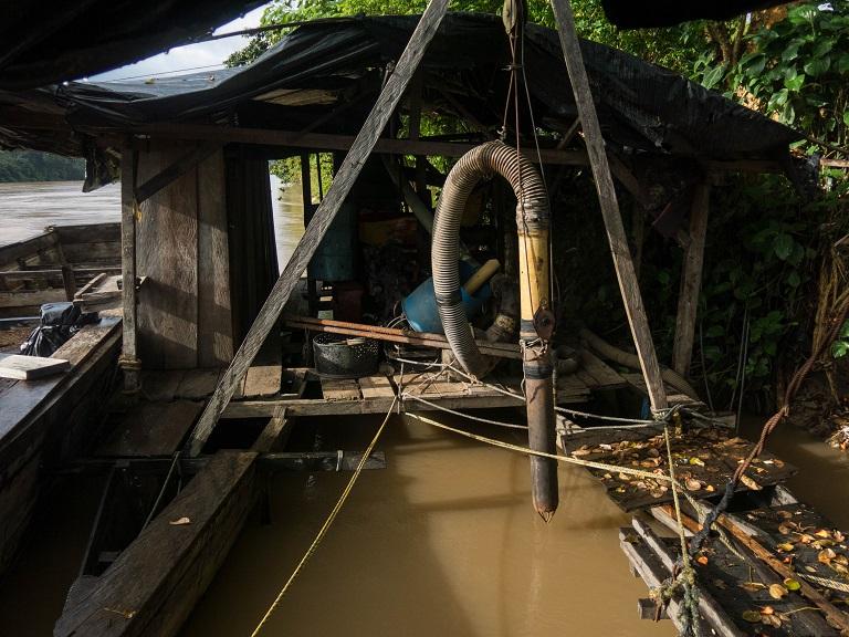 Un tubo grande se usa para dragar los cauces del río en busca de oro. Foto de Bram Ebus para Mongabay