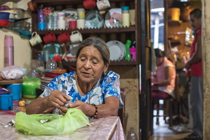 Señora Juana limpiando las semillas mientras habla sobre los engaños de la empresa Comexhidro. Foto: Martina Zoldos.