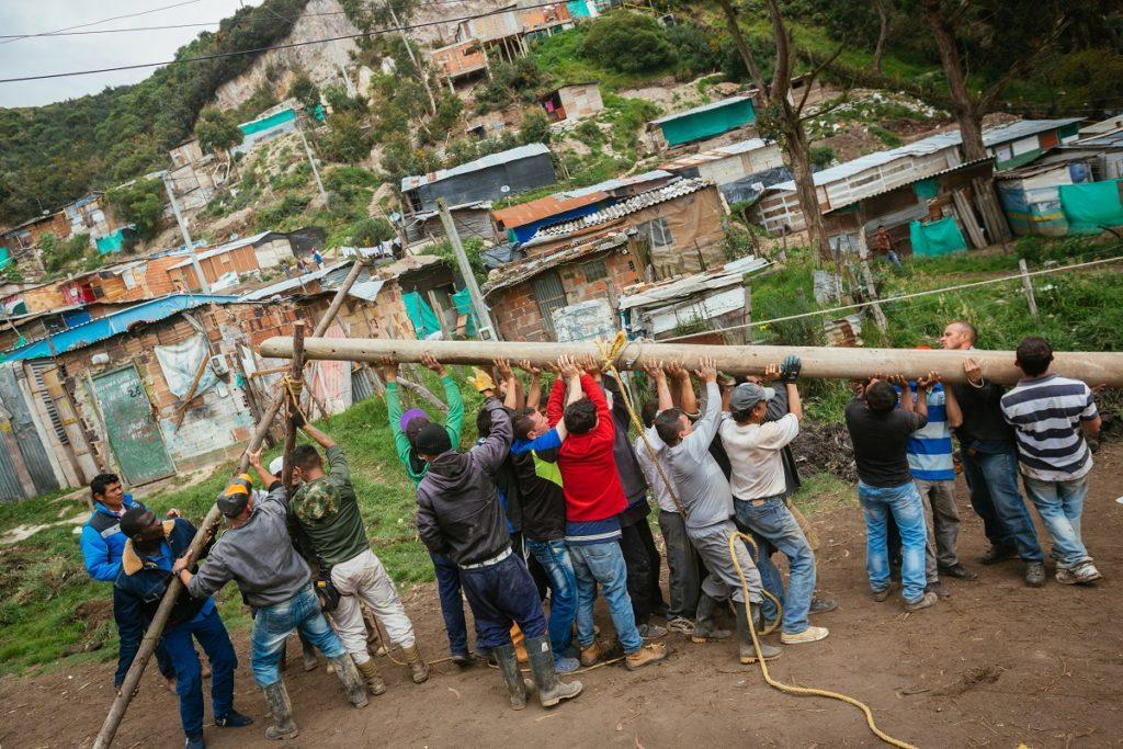 Miembros de la comunidad trabajan juntos para instalar postes de luz. Foto cortesía de Ana Cristina Vallejo.