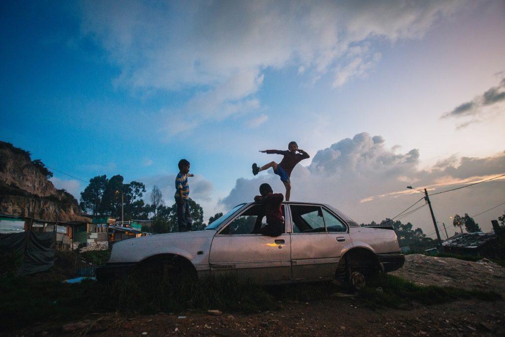 Niños que juegan en un auto abandonado, mientras el sol se pone sobre San Germán. Foto cortesía de Ana Cristina Vallejo.