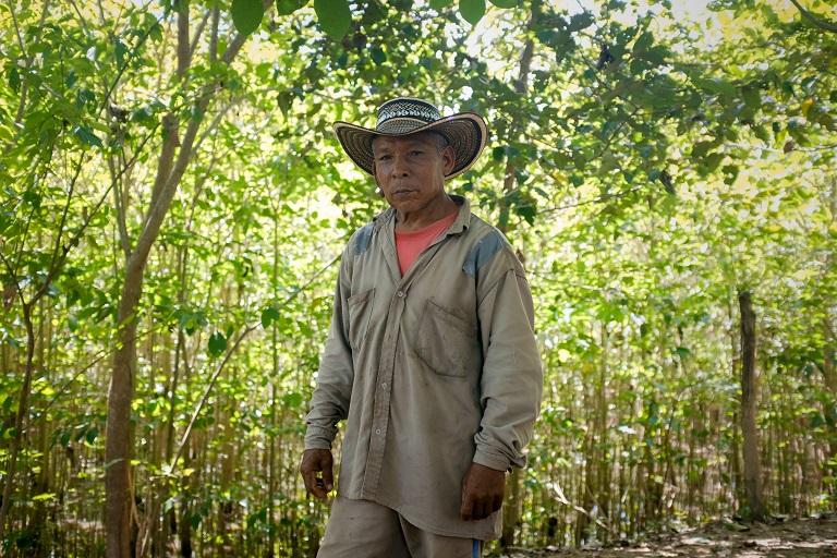 Argemiros Capela en su parcela frente a un pequeño fragmento de bosque que ha empezado a crecer después de años de desertificación, Montes de María. Foto de Ana Cristina Vallejo/Mongabay.