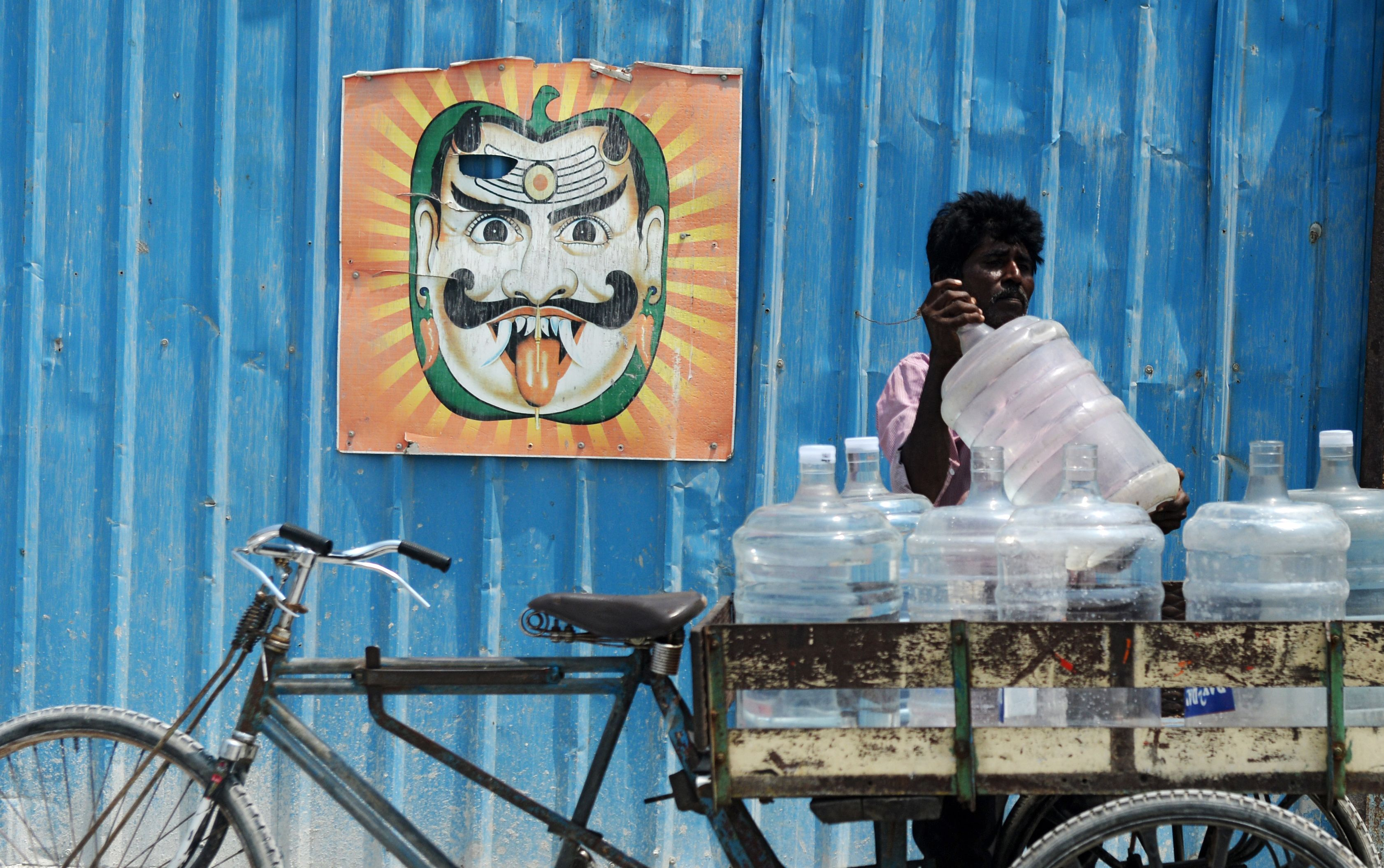 TOPSHOT - An Indian water vendor loads his cart with 20 litre water bottles in Chennai on March 21, 2018. International World Water Day is marked annually on March 22 to focus global attention on the importance of water and to advocate for sustainable water resource management. / AFP / ARUN SANKAR