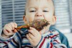 70760105-el-niño-que-come-con-avidez-de-pollo-grasa-y-deliciosa-en-la-cocina-muy-hambriento