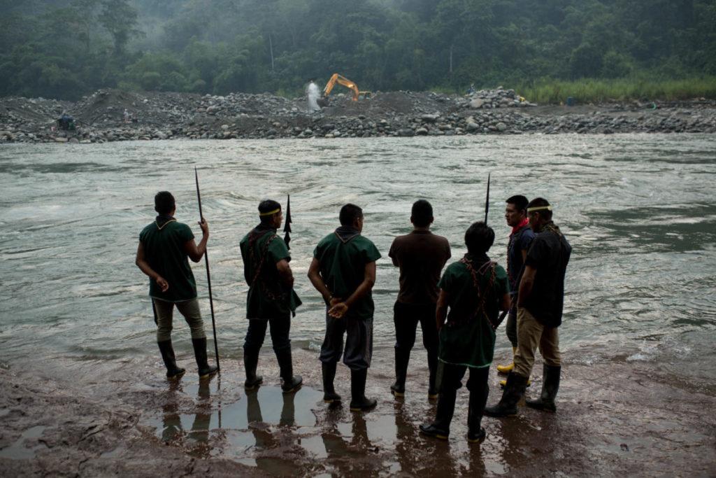 Miembros de la comunidad indígena Cofán de Sinangoe caminan a orillas del río Aguarico, mientras al fondo se ve una retroexcavadora removiendo tierra. Foto: Jerónimo Zuñiga/Amazon Frontlines.